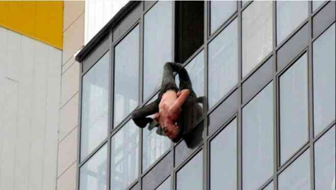擦窗工人倒挂15楼窗外半小时 裤管被勾保命
