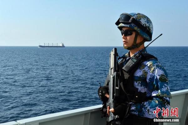 """中国海军第22批护航编队官兵新年联欢 当地时间1月1日上午9时,巴哈马籍""""伊万爱丽儿""""号杂货船在中国海军第22批护航编队和第21批护航编队的共同护送下,从亚丁湾西部海域向阿拉伯海索克特拉岛北部海域开进,这标志着海军第22批护航编队在新年正式接替执行护航任务。图为特战队员袁杰正在对被护船舶加强警戒。"""