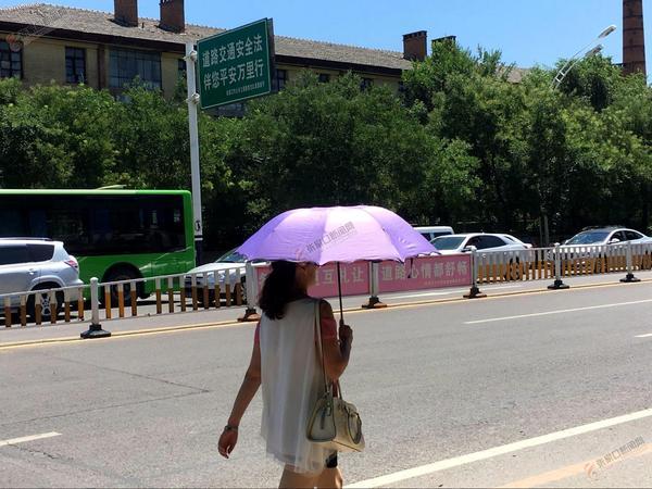 【创城进行时】三伏天来了,张家口市民出行多注意 行人撑太阳伞防晒。王�E摄