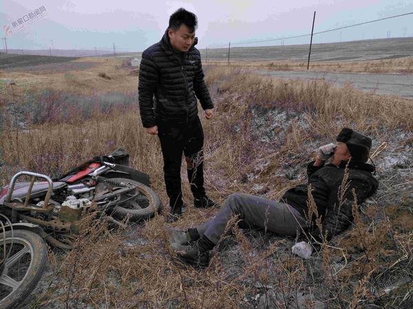 村民骑摩托掉边沟 扶贫干部路遇施救 艾唯一(左)正在救助伤者。