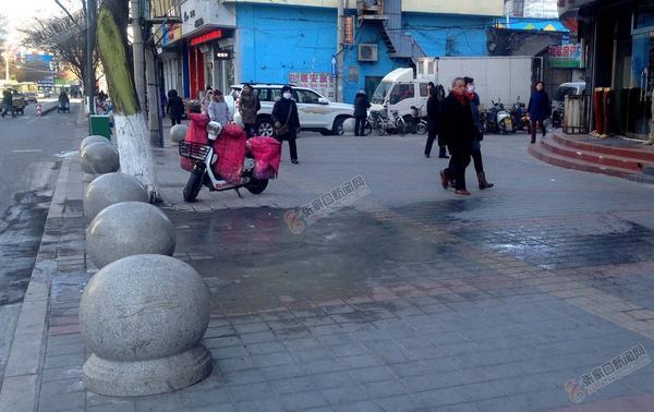 商户泼倒脏水路面结冰 市民经过薄冰绕道行走。 吕慧 摄