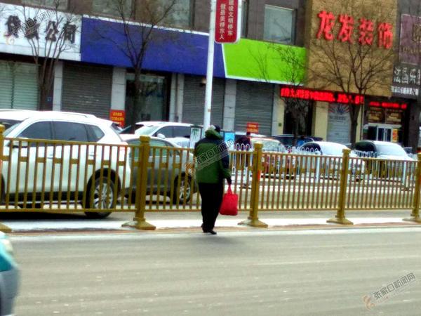 马路中间信步走,危险! 一名老人走在马路中央。 冀泽民 摄