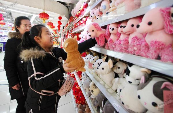 狗年吉祥物走俏 图为小朋友在商场内挑选狗年吉祥物。 和颖 摄