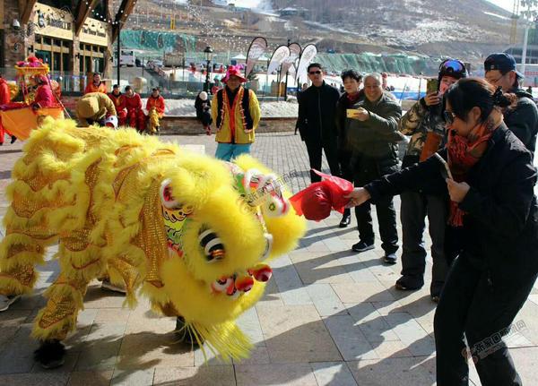 【新春走基层】舞龙舞狮悦游客 舞狮表演吸引游客拍照留念。