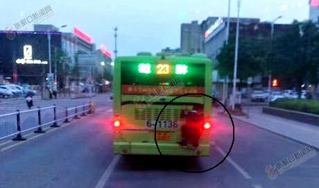危险!张家口一男生扒公交车尾蹭车惊呆路人 照片中,这位男生扒在公交车尾部,十分危险。