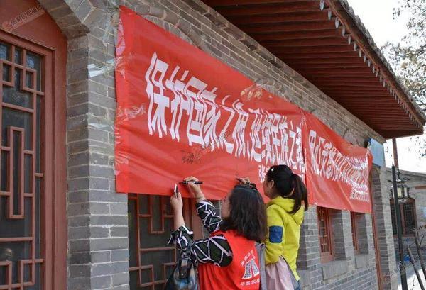 记张家口义工联合会文物保护队 文物保护队悬挂条幅,志愿者进行签名,号召大家保护文物。