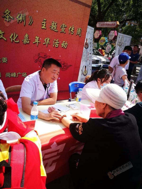 """张家口市举办中医药""""一法一条例""""宣传活动 省名中医、市中医院副院长王永利在为市民义诊"""