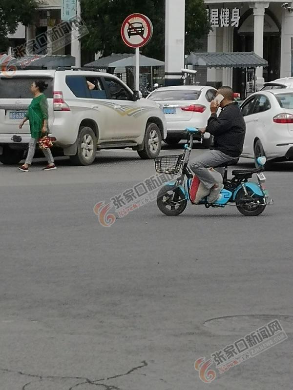 【交通违法行为曝光台】骑车接打电话很危险 边打电话边骑车的市民。 孙媛 摄