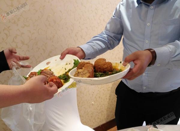 """好面子婚宴变成""""剩宴"""" 食客将剩菜打包准备回家喂狗。 陈嘉 摄"""