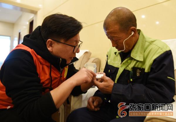 张家口宣化:澳洲魏基成天籁列车慈善基金会爱心捐助听障人士 助残志愿者帮助听障人士佩戴助听器。