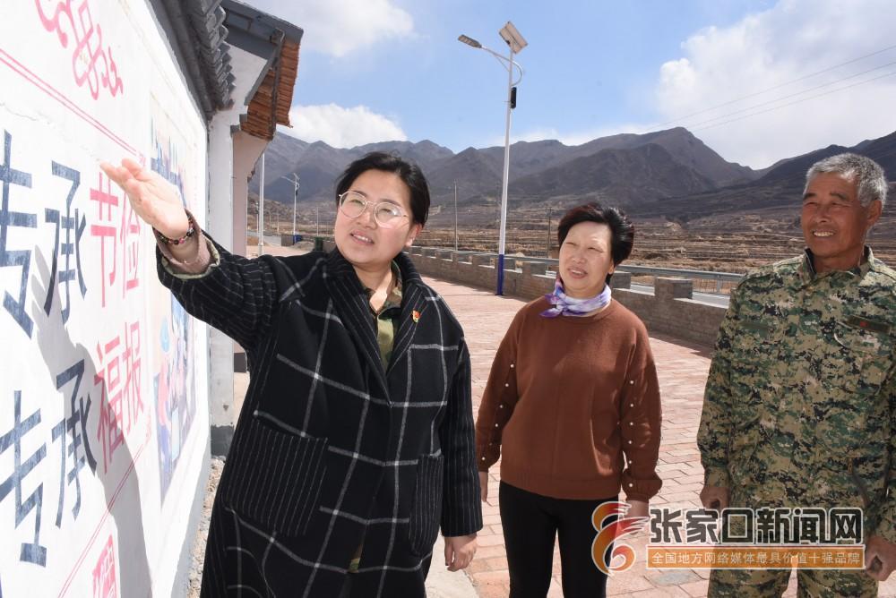 【新时代 新青年】赵娟:奋斗青春放飞梦想 1赵娟 (左一)和村民在文化墙前。