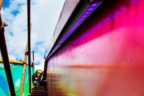 京張高鐵官廳水庫特大橋首批上弦桿洗墻燈調試點亮 工人在大橋拱型鋼桁梁上安裝調試亮化燈。