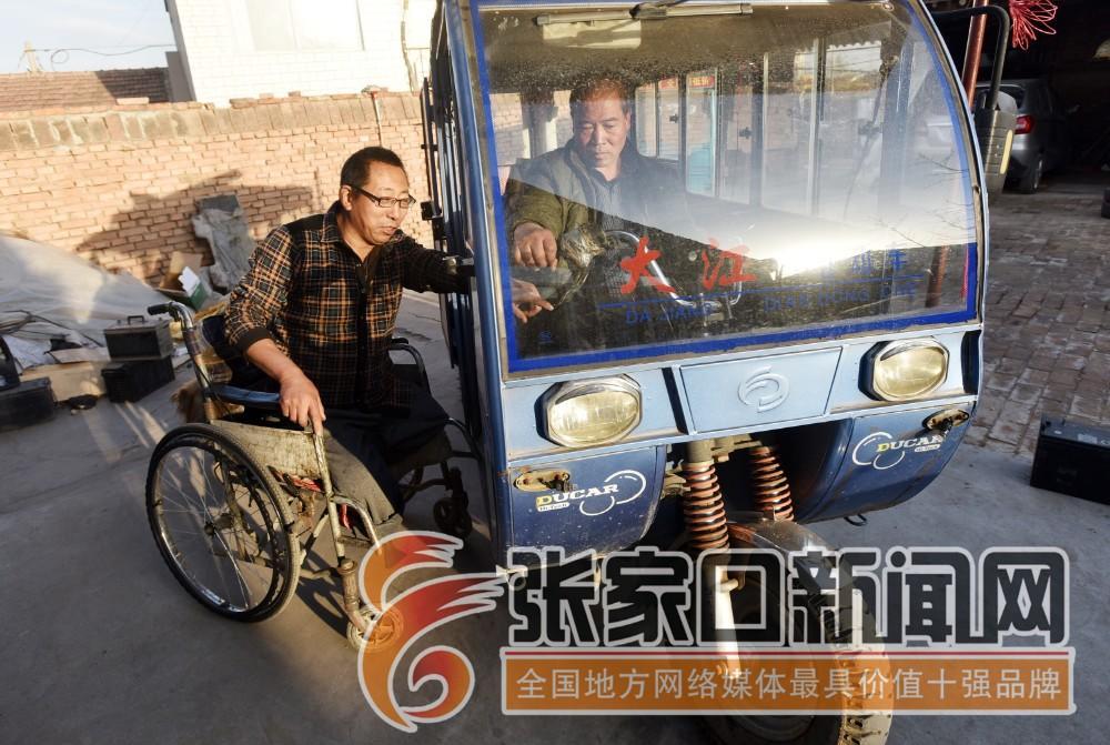 """张家口宣化:""""无腿硬汉""""武功亮 武功亮向村民了解故障车辆情况。"""