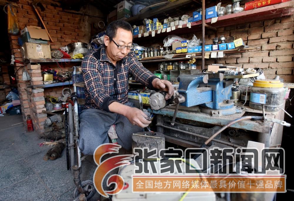 """张家口宣化:""""无腿硬汉""""武功亮 在简陋的维修室武功亮认真维修汽车马达。"""